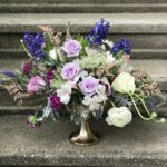 Gold compote arrangement with lavender spring blooms