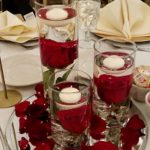 Cylinder vase set with submerged roses and floating candles.