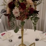 Tall centerpiece with blush and wine colored flowers