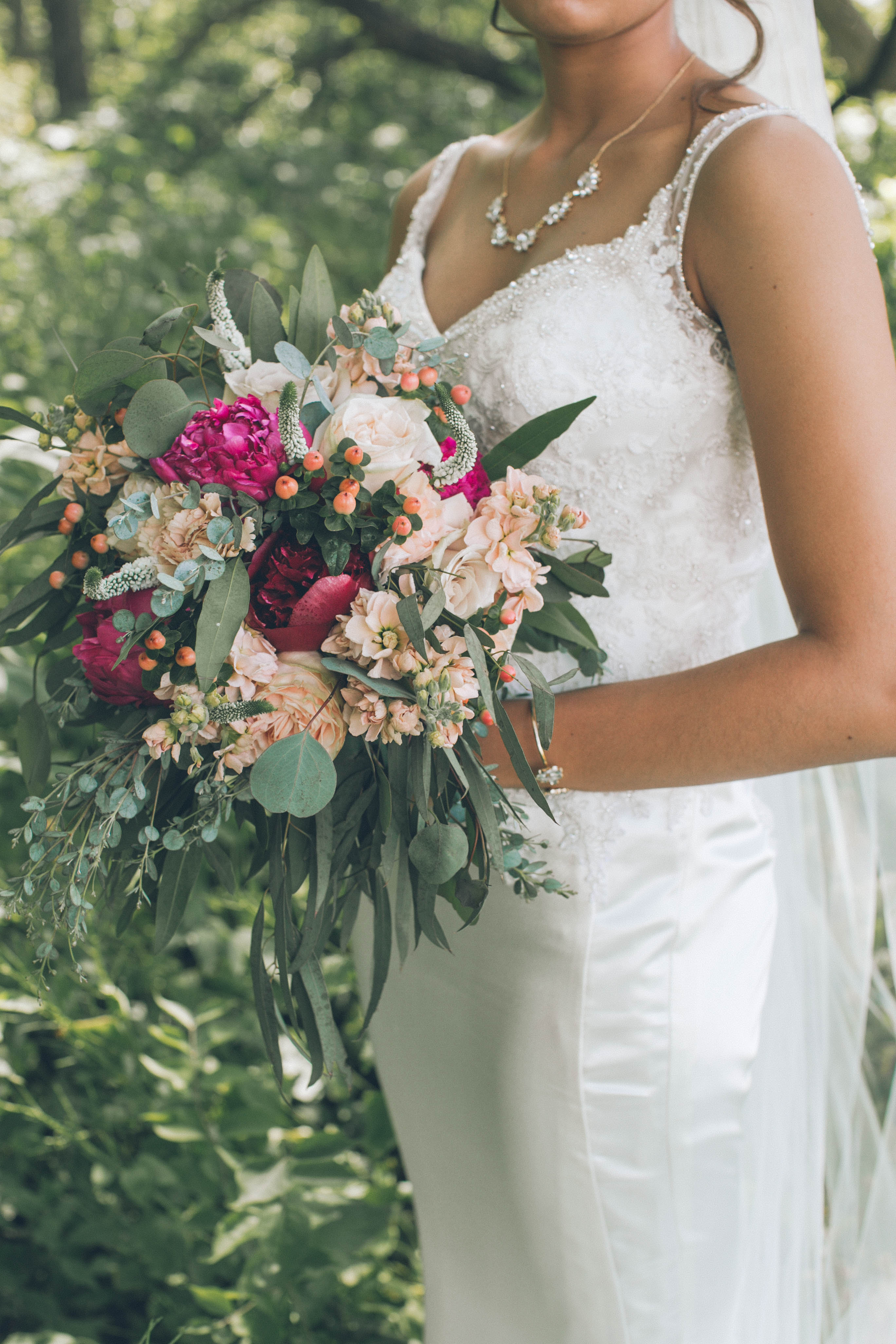 Bridal bouquet with hot pink peonies, peach stock and pink roses with eucalyptus.