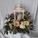 lantern surrounded by flowers in a wooden box centerpiece