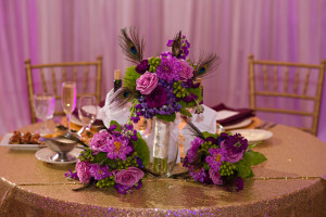 Head Table decor, gold sparkly linens, peacock themed reception decor