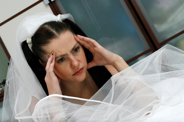 The headache is represented on the face of the beautiful bride in a wedding dress near a bed