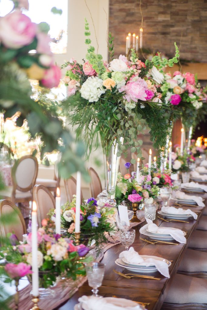 Wedding reception decor using tall clarinet vase arrangements spilling over with greens and pastel blooms.