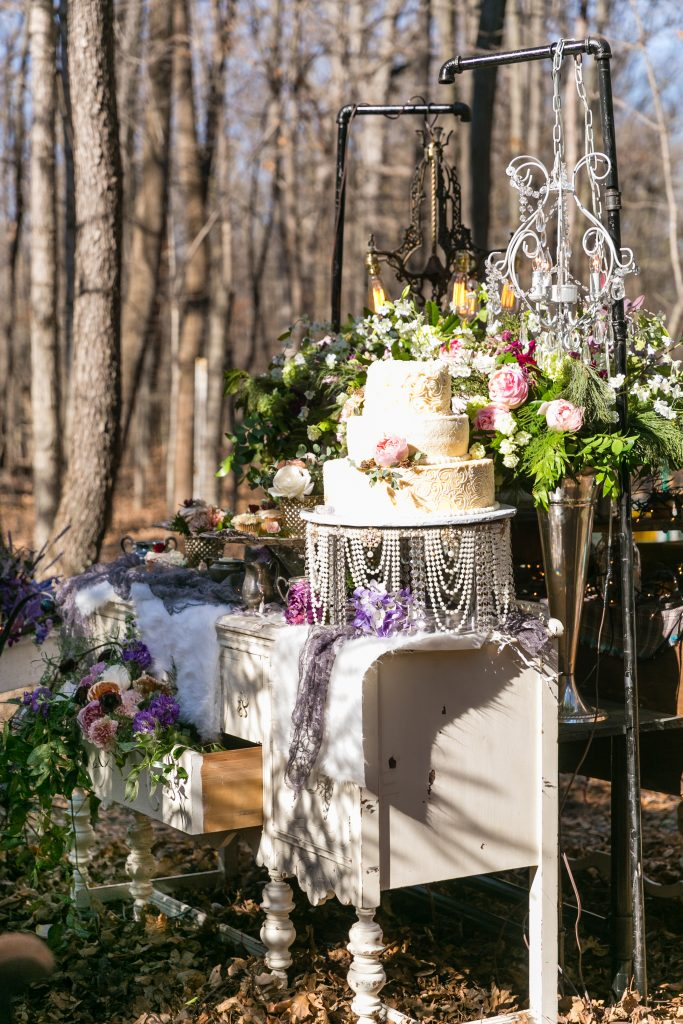 Bohemian wedding decor using vintage buffet for desserts with flowers and greens spilling out of the buffet drawer.